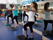 Différentes femmes d'âge ayant le train aérobie de groupe dans le club de sport Image stock