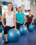 Différentes femmes d'âge d'ordinaire sautant sur la boule d'exercice Photo libre de droits