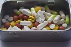 Différentes pilules de couleur dans une boîte en métal Images stock