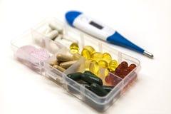Différentes pilules, médicaments, les pilules dans la boîte pour le plan rapproché de drogues avec le thermomètre sur le fond bla Image libre de droits