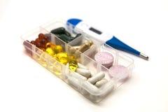 Différentes pilules, médicaments, les pilules dans la boîte pour le plan rapproché de drogues avec le thermomètre sur le fond bla Photo libre de droits