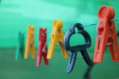 Différentes pinces à linge colorées formées accrochant sur la corde à linge Images libres de droits