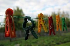 Différentes pinces à linge colorées formées accrochant sur la corde à linge Photo libre de droits