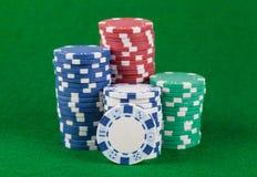 Différentes puces de casino sur une table verte Photo stock