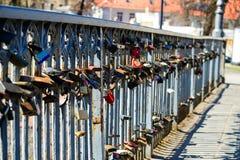 Différentes serrures d'amour attachées à la grille en métal d'un pont dans E Photographie stock
