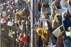 Différentes serrures d'amour attachées à la grille en métal d'un pont dans E Image stock