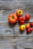 Différentes tomates criquées d'héritage au-dessus de vieille table en bois, vue supérieure Photos stock