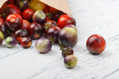 Différentes tomates dans le sac de papier sur le fond en bois blanc Photos libres de droits
