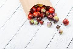 Différentes tomates dans le sac de papier sur le fond en bois blanc Photo stock