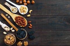 Différents écrous assortis, pruneaux, graines de citrouille dans des cuillères sur un fond en bois foncé Photos libres de droits