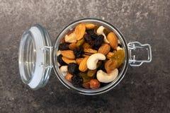 Diff?rents ?crous organiques savoureux dans le pot en verre sur la table fonc?e Nourriture et casse-cro?te sains images stock