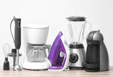 Différents appareils de ménage et de cuisine sur la table sur le fond léger Élément intérieur image stock
