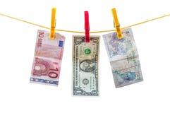 Différents billets de banque de devise accrochant sur la corde à linge Photos libres de droits