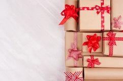 Différents cadeaux avec le plan rapproché rouge d'arcs sur le fond en bois blanc, vue supérieure, l'espace de copie images libres de droits