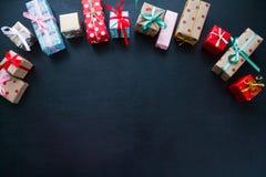 Différents cadeaux de Noël sur un fond noir images stock