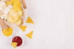 Différents casse-croûte d'or sur la sauce à papier de métier, à nachos de triangles, rouge et jaune dans la cuvette sur le fond e photo libre de droits