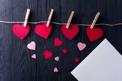 Différents coeurs avec les pinces à linge et la feuille blanche Photo libre de droits