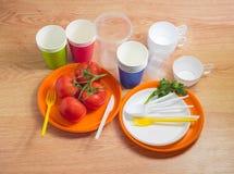 Différents couverts et tomates jetables sur une table en bois Photographie stock libre de droits