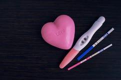 Différents essais de grossesse positifs avec un coeur rose Photos stock