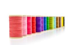 Différents fils de couture de couleur sur un petit pain Image libre de droits