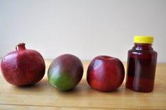 Différents fruits et une bouteille de jus sur une surface en bois images libres de droits
