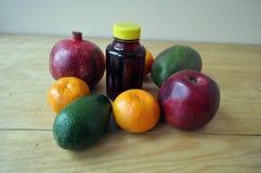 Différents fruits et une bouteille de jus sur une surface en bois photos stock