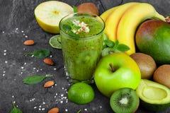 Différents fruits exotiques et cocktail vert de kiwi sur un fond en pierre gris-foncé Ingrédients organiques pour des régimes image libre de droits