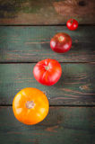 Différents genres colorés de tomates sur le fond en bois Image stock