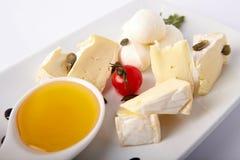Différents genres de cheeseon un plat blanc images stock
