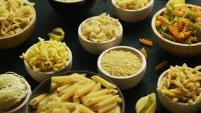 Différents genres de macaronis mis dans des cuvettes banque de vidéos