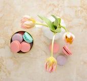 Différents genres de macarons sur le fond et les tulipes de marbre Images libres de droits
