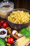 Différents genres de pâtes, de tomates-cerises et d'épices Photographie stock