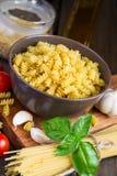 Différents genres de pâtes, de tomates-cerises et d'épices sur un b foncé Photographie stock