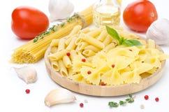 Différents genres de pâtes italiennes, tomates fraîches, huile d'olive Photographie stock