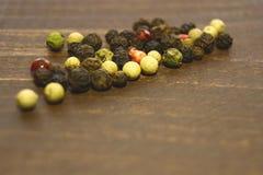 Différents genres de poivre sont dispersés sur la table Image stock