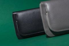 Différents portefeuilles en cuir sur la tirette Fond vert Images stock