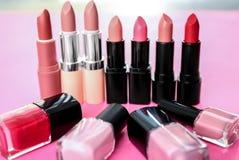 Différents rouges à lèvres et vernis à ongles sur le fond de couleur Cosm?tique professionnel photo stock