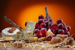 Différents types de fromage, de couteau de vintage et de fourchette pour le fromage et des raisins image libre de droits
