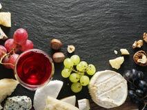 Différents types de fromages avec le verre et les fruits de vin Photo libre de droits