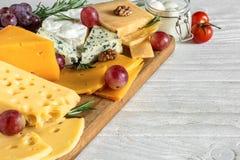 Différents types de fromages sur la planche à découper en bois Photographie stock