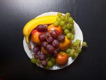 Différents types de fruits d'un plat en céramique blanc sur un Ba noir Photo stock