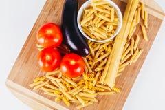 Différents types de pâtes italiennes crues avec des tomates et d'autres légumes, fond de vue supérieure Orientation choisie Photos stock