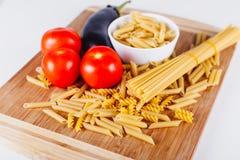 Différents types de pâtes italiennes crues avec des tomates et d'autres légumes, fond de vue supérieure Orientation choisie Photos libres de droits