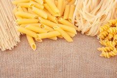 Différents types de pâtes sur la toile de jute Photos stock