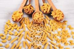 Différents types de pâtes se situant dans des cuillères en bois Photo libre de droits