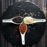 Différents types de riz dans des cuillères sur le fond noir photo libre de droits