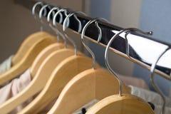 Différents vêtements sur haut étroit de cintres Image stock