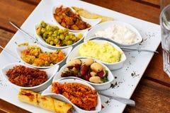 Differen开胃菜和反pasti在白色板材在咖啡馆或休息 免版税库存照片