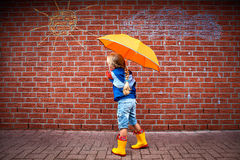 Difference. A little girl with an umbrella in front of a wall with a sketch of a sun and a rain cloud Royalty Free Stock Photos
