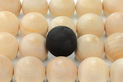 Difference. Group of wooden bolls same in size, colour, texture representing the crowd, a ball coloured in black higher than others and on focus representing Stock Photos